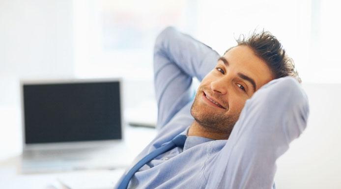 Junger mann sitzt entspannt mit Händen hinter dem Kopf verschränkt am Arbeitsplatz, den Kopf zu uns gewendet