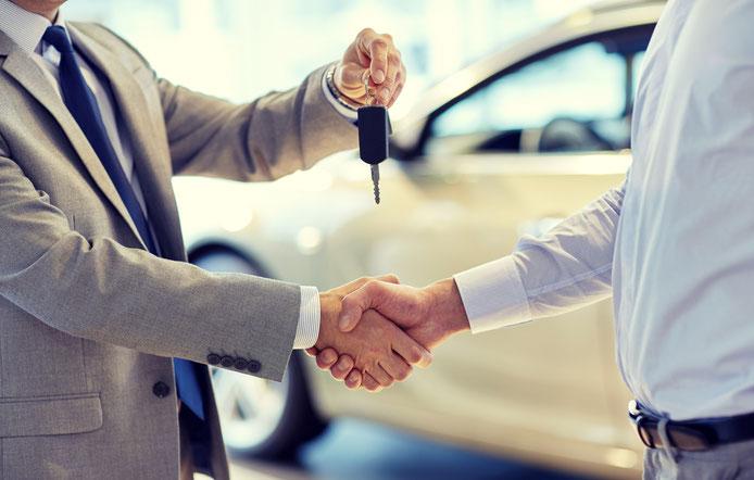 Zwei Menschen geben sich die Hand und tauschen Auto Schlüssel aus