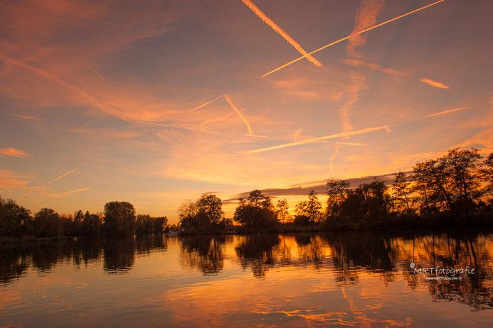 Zonsondergang bij de Vecht met reflecterende vliegtuigstrepen
