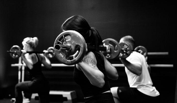 Drei Personen im Fitnessstudio trainieren mit einer Langhantel auf dem Rücken den Ausfallschritt.
