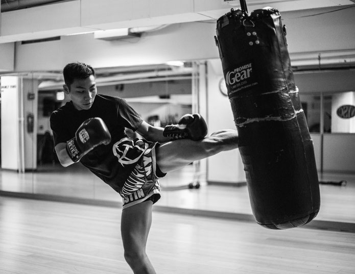 Ein Muay Thai-Schüler trainiert und tritt gegen einen Boxsack.