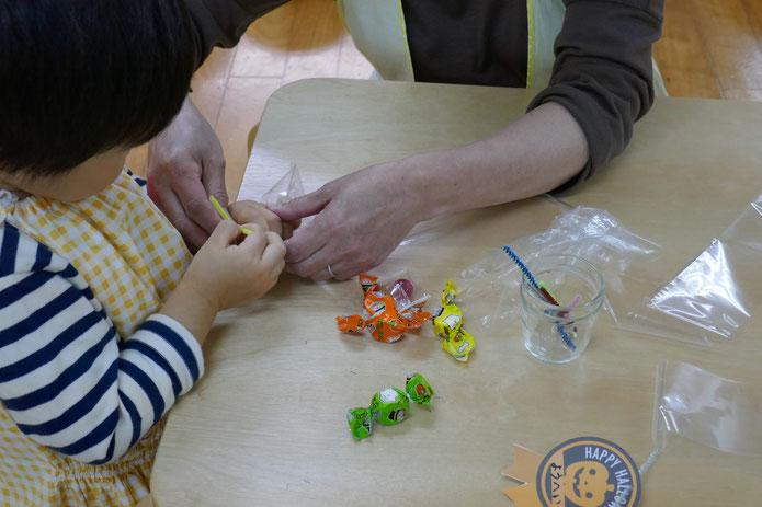 2歳児のモールを使ったキャンディレイの製作を先生が援助。いっしょに行いながら、ひとつひとつの動作を学んでいます。