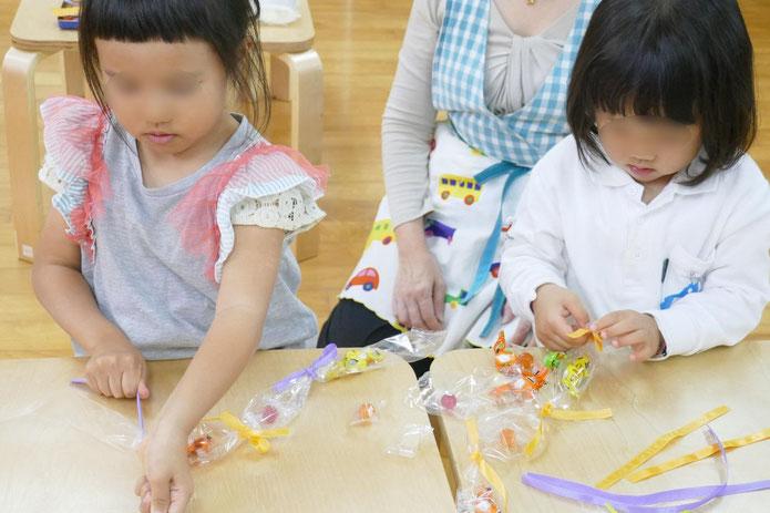 幼稚園児は、ひもを使って丸結びやちょうちょ結びをおこないながら、キャンディレイをつくっています。