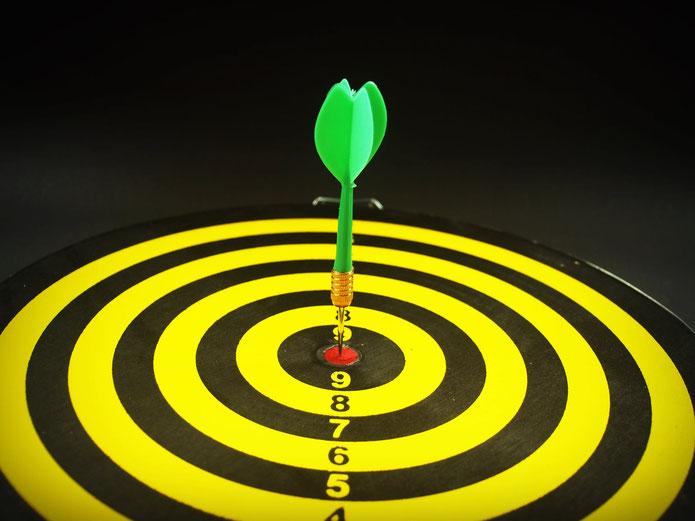 Zielscheibe mit Pfeil im Zentrum