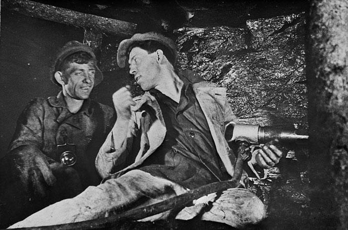 Aleksej Stachanov (al centro), minatore russo, icona ed eroe del lavoro, parla con un altro minatore