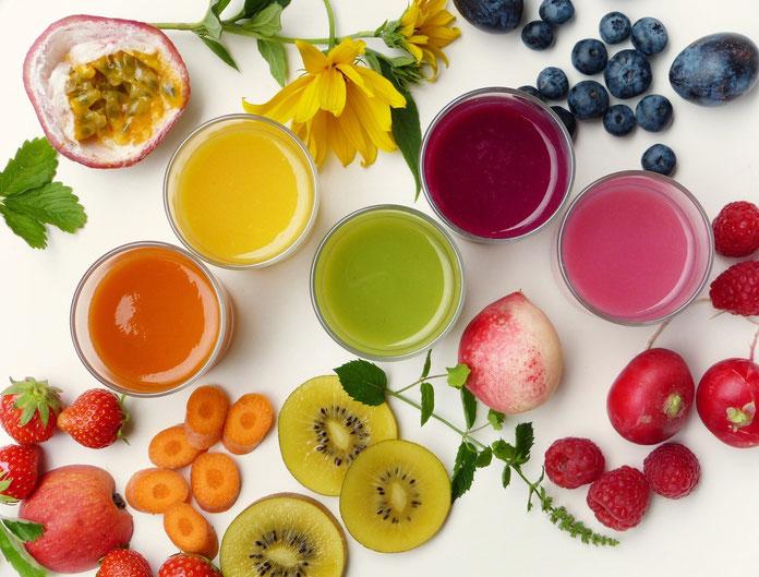 Tisch mit bunten Smoothies, gesundes Obst, Heidelbeeren, Kirschen, Kiwi, Erdbeeren