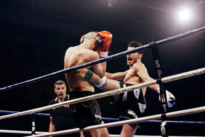 Zwei Thaiboxer kämpfen in einem Boxring. Der rechte Thaiboxer tritt mit einem Schienbein in die Rippen des Gegners. Im Hintergrund steht der Wettkampfrichter.