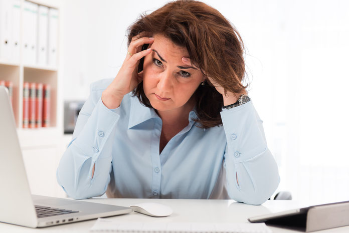 Frau gestresst im Büro; Kurtz Wirtschaftsdetektei Nürnberg
