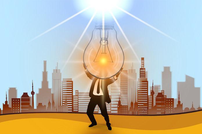 Man von Glühbirne erhellt steht vor einer Stadt
