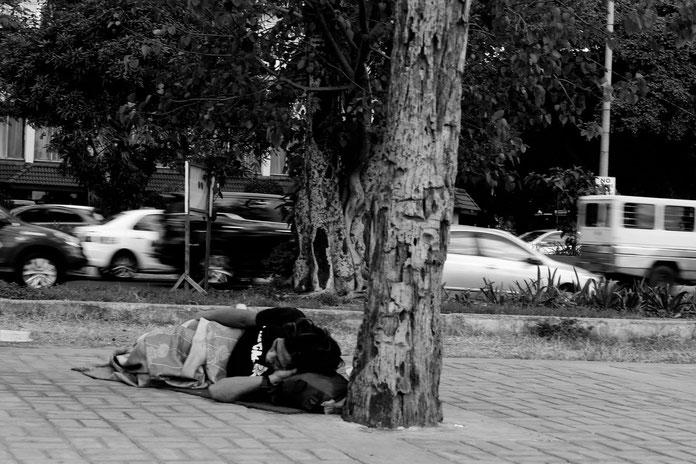 Obdachlose Person schläft auf Straße