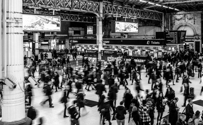 Menschenmenge auf Bahnhof in Schwarz-Weiß