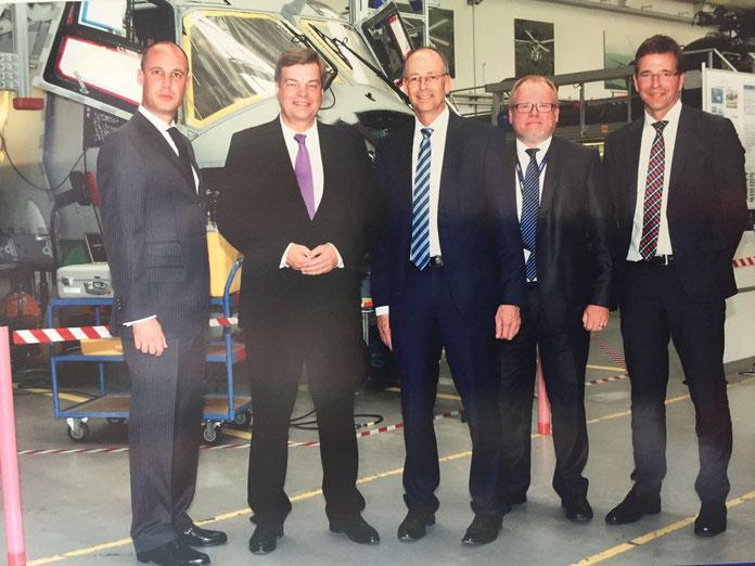 PSts Ferlemann und  Dr. Wolfgang Schoder Geschäftsführung CEO (Mitte),  mit weiteren Mitgliedern der Geschäftsführung vor dem NH 90 Sea Lion