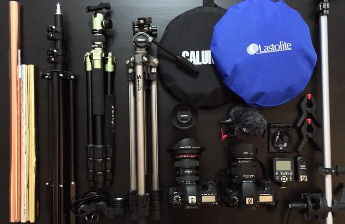 Fotografie-Ausrüstung mit mehreren DSLR-Kameras, Stativen, Reflektoren und anderen Hilfsmitteln.