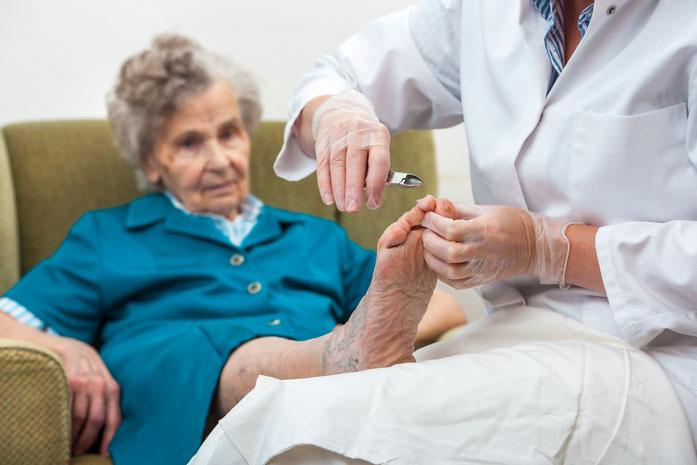 Pflegebedürftige Seniorin erhält die Fußnägel geschnitten, Kurtz Detektei Berlin