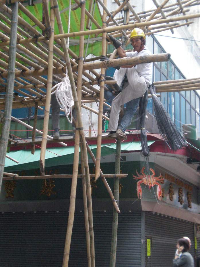 « Temple St. bamboo scaffolding 2 » par BrokenSphere — Travail personnel. Sous licence CC BY-SA 3.0 via Wikimedia Commons - https://commons.wikimedia.org/wiki/File:Temple_St._bamboo_scaffolding_2.JPG#/media/File:Temple_St._bamboo_scaffolding_2.JPG