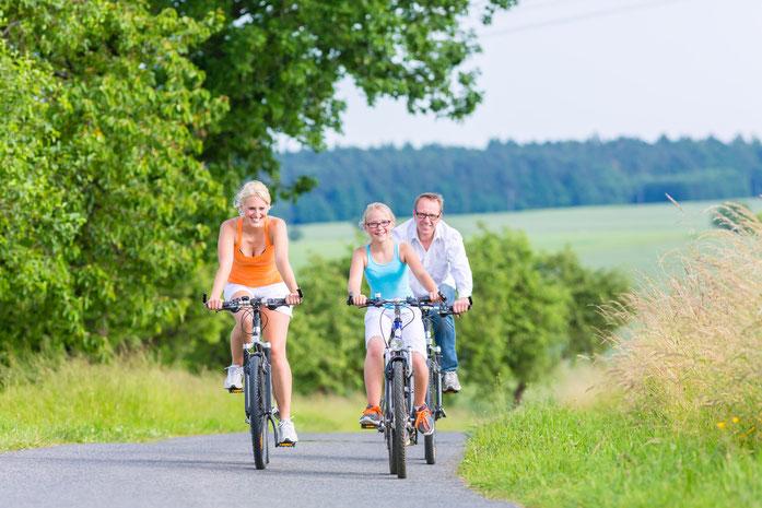 Eltern mit Tochter bei einem Fahrradausflug im Grünen; Kurtz Detektei Hannover