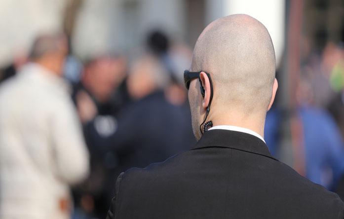 Mann mit Glatze und Ear-Set im Anzug blickt auf Menschenansammlung; Kurtz Detektei Hannover