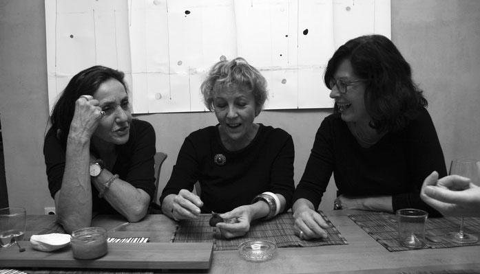 Drei Frauen sitzend am Tisch beim Gespräch während der Kunstausstellung Kraus // Kröner // Wolter vor einem Bild von Harald Kröner