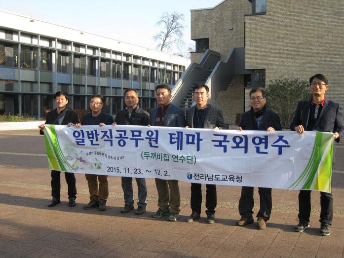 Foto von internationalen Besuchern vor dem Schulgebäude der Grundschule Niederheide