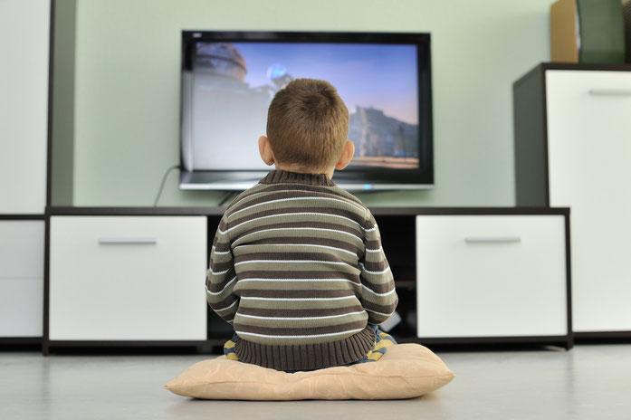 Kleiner Junge sitzt allein auf einem Kissen auf dem Fußboden vor einem Fernseher; Sorgerecht, Kurtz Detektei Nürnberg.