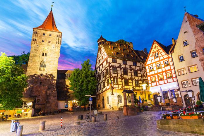 Nächtliche Aufnahme der angestrahlten Gebäude am Tiergärtnerplatz in Nürnberg, Fachwerkhäuser und ein Turm; Detektive der Kurtz Detektei Nürnberg