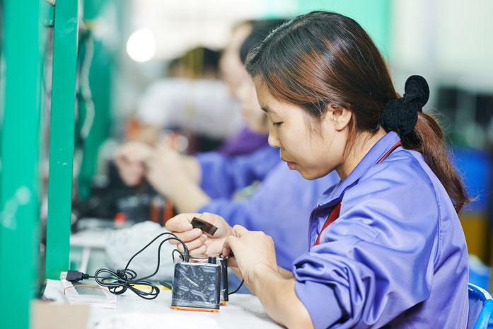 Asiatische Frau arbeitet in einer Manufaktur an einem elektronischen Gerät; Kurtz Detektei Nürnberg
