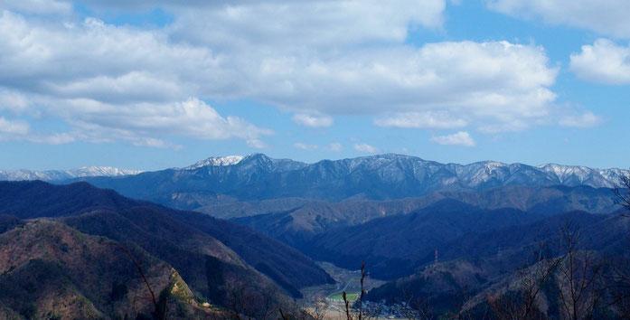 山頂から望む東方の山々。雪をかぶった山の手前が冠山でしょう。その左が金草山です。      その中腹を高倉峠への林道が横切っている。