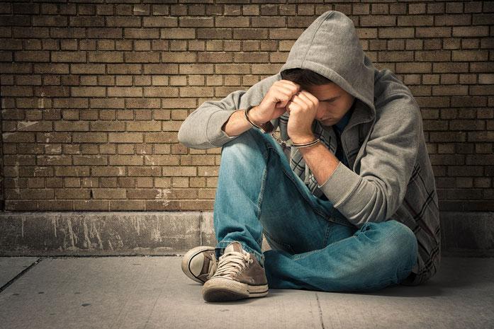 Jugendlicher in Handschellen auf dem Boden vor einer Mauer sitzend; Kurtz Detektei Essen