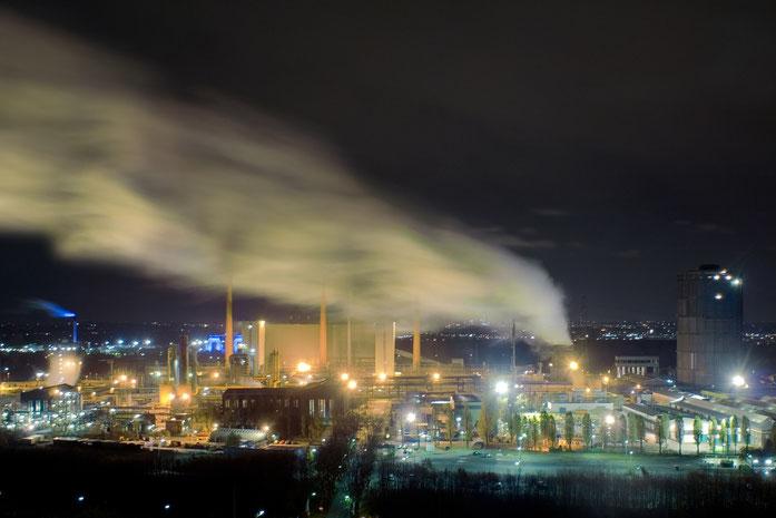 Industrieanlage bei Nacht mit aufsteigendem Rauch in Essen, Kurtz Detektei Essen