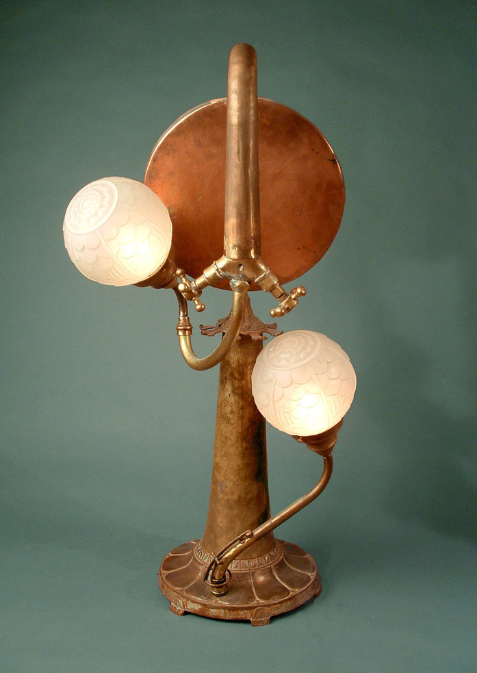 Assemblage light art sculpture made from brass and copper pieces and art deco glass. The brass and copper pieces include a faucet turned upside down, a musical instrument bell, and a pan from a balance scale.