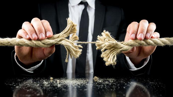 Ein Mann im Anzug hält ein Seil in beiden Händen, das in der Mitte nur durch einen dünnen Strang zusammengehalten wird; Stuttgarter Detektive