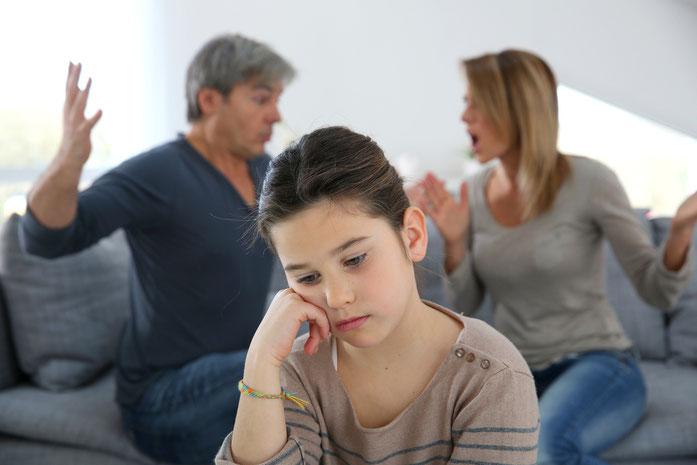 Eltern streiten sich im Hintergrund, im Vordergrund stützt das gemeinsame Kind traurig den Kopf auf die Hand; Kurtz Detektei Stuttgart