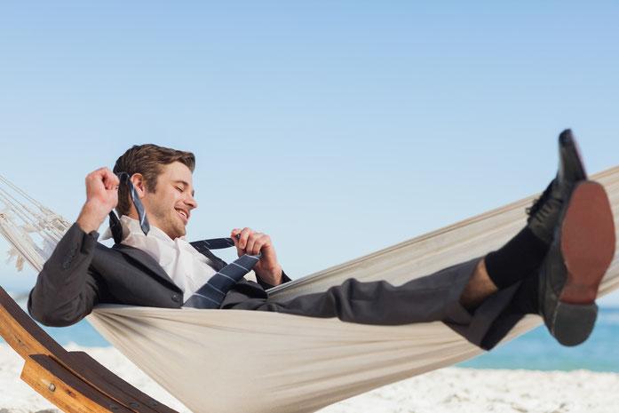 Ein Geschäftsmann liegt am Strand in der Hängematte und entledigt sich bei strahlendem Himmel seiner Krawatte; Kurtz Detektei Stuttgart