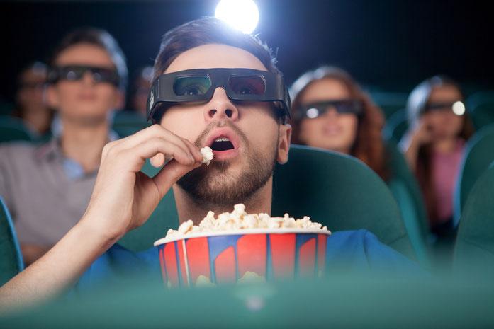Ein Mann sitzt mit 3D-Brille im Kino und isst Popcorn, im Hintergrund weitere Besucher; Kurtz Detektei Stuttgart