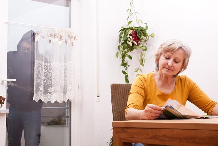 Frau mittleren Alters sitzt am Küchentisch und liest eine Zeitschrift. Im Hintergrund versucht ein vermummter Einbrecher, die Eingangstür zu öffnen. Die Detektive der Kurtz Detektei Stuttgart ermitteln gegen Wohnungseinbrecher.