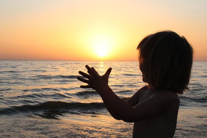 Photographie d'une petite fille joignant les mains devant un coucher de soleil sur la mer