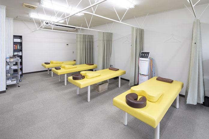 たきがみ鍼灸整骨院、明るい黄色のベッドが4台あります。