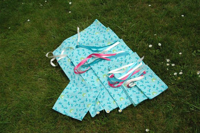"""Il s'agit ici des pochettes de l'Emballage qui Voyage, cousues dans le tissu """"Grenouilles et Libellules"""", de couleur turquoise avec des rubans rose, crème et turquoise."""