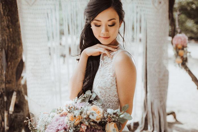 Schön geschminkte Braut mit hochgesteckten Haaren mit einem Brautstrauß und einem wunderschönen vintage Hochzeitskleid aus Spitze.