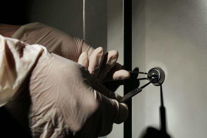 Behandschuhte Hände versuchen, mit Lockpicking-Werkzeug ein Schloss zu öffnen. Kurtz Detektei Hamburg