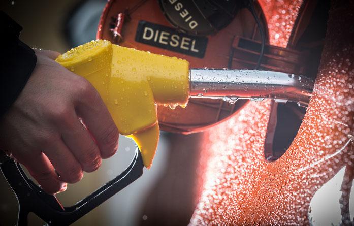 Männliche Hand hält Einfüllstutzen und betankt ein rotes Fahrzeug mit Diesel-Treibstoff; Kurtz Detektei Hamburg.