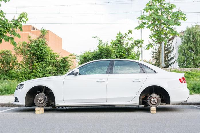 Weißes Auto mit gestohlenen Rädern, das auf Holzblöcke aufgebockt wurde; Kurtz Detektei Hamburg