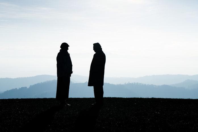 Die Silhouetten zweier Männer, die sich auf einer Anhöhe gegenüberstehen; Detektive der Kurtz Detektei Hamburg