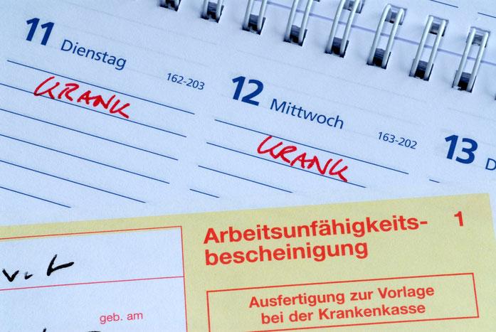 """Bild eines Kalenders mit Eintragungen """"krank"""" und einer Arbeitsunfähigkeitsbescheinigung; Mitarbeiterüberwachung durch die Detektive der Kurtz Detektei Hamburg"""