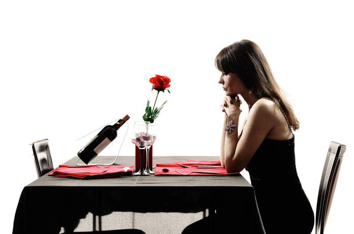 Frau sitzt einsam im schwarzen Abendkleid am gedeckten Esstisch; Kurtz Detektei Düsseldorf