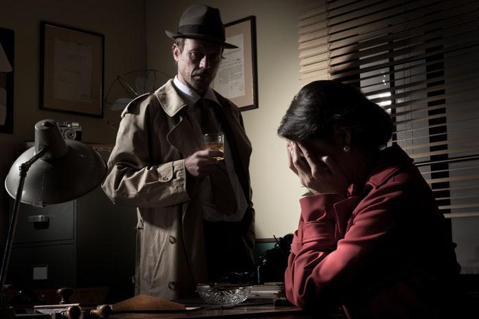 Stereotyper Detektiv in seinem Büro mit einer rot gekleideten Klientin; Kurtz Detektei Düsseldorf