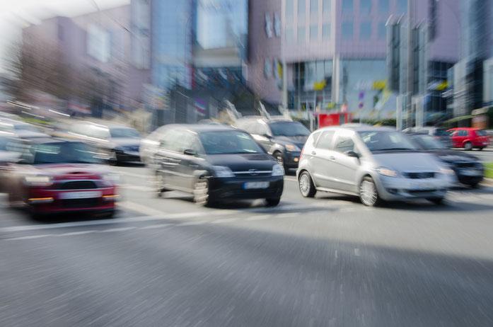 Mehrere Fahrzeuge fahren in einem verzerrten Bild von einer Ampel los; Kurtz Detektei Düsseldorf.