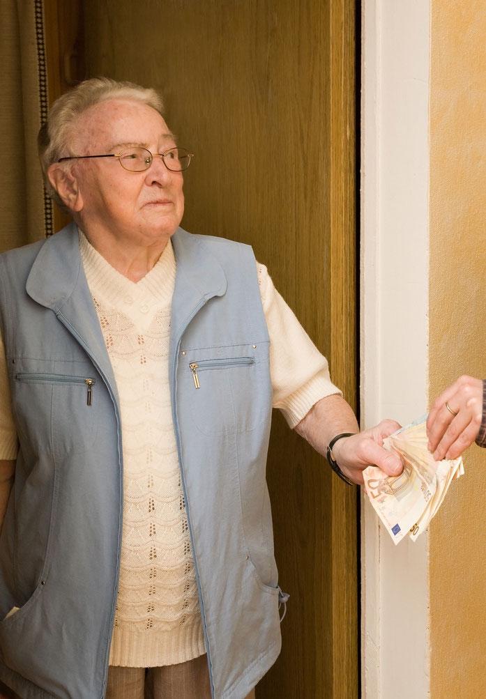 Rentner übergibt mit skeptischem Blick Geld an Unbekannten an der eigenen Wohnungstür
