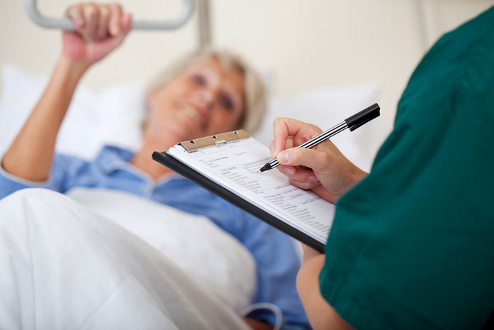 Seniorin im Bett, während der Arzt Notizen auf dem Klemmbrett macht, Kurtz Detektei Köln