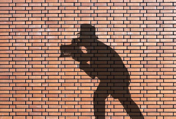Privatdetektive Kurtz Detektei Köln; Schatten eines Detektivs auf einer Mauer während einer Observation